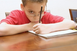 Left handed young boy wearing glasses reluctant to do homework